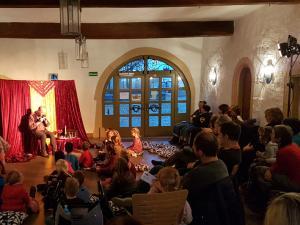 Märchenerzähler erzählt in einer Bibliothek Kindern und Erwachsenen
