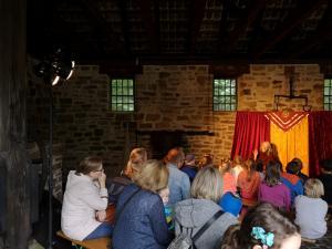 Märchenerzählerin mit Publikum im Freilichtmuseum