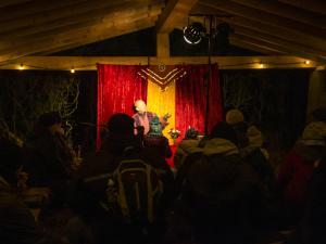 Märchenerzähler Karlheinz Schudt mit Publikum beim Weihnachtsmarkt im Wald